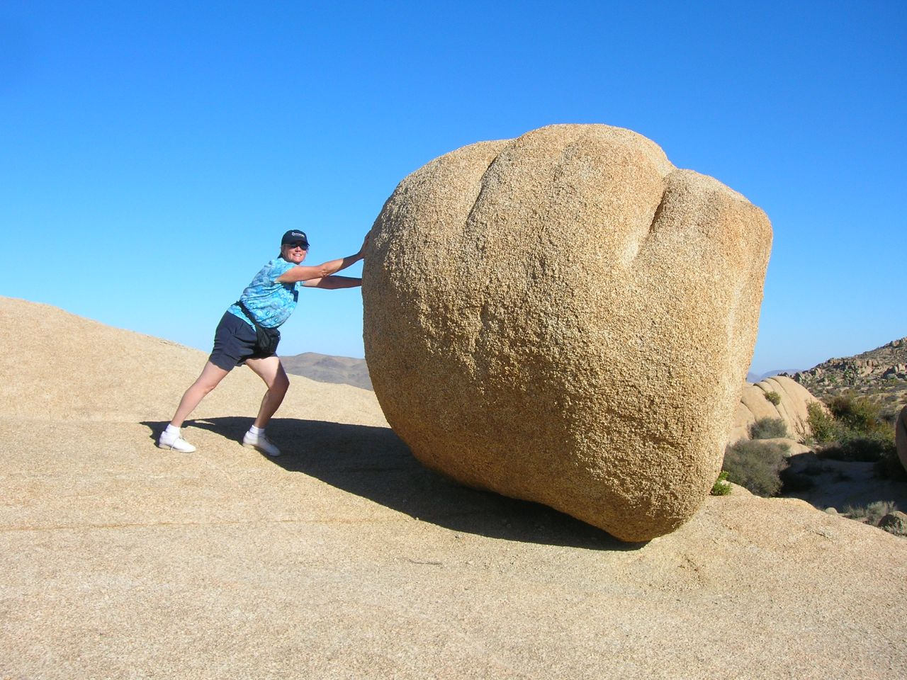 person pushing boulder